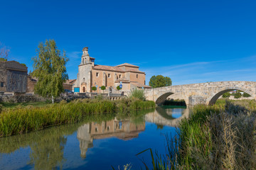 church of Santa Cristina and stone roman footbridge, reflected on water of Ucero river, landmark and public monument in Burgo de Osma, Soria, Spain, Europe