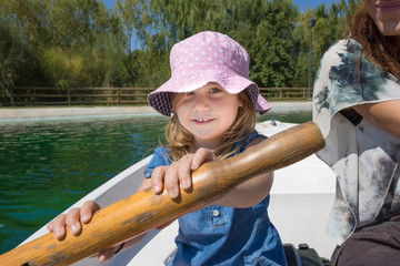 Four years old blonde girl with hat sitting in boat paddling next to woman mother, looking and smiling happy, at park lake