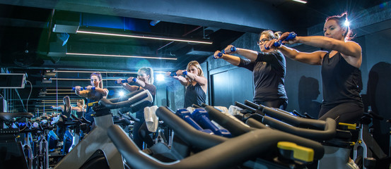 Panoramic view of sporty girls doing exercises with weights while riding fitness bike in gym