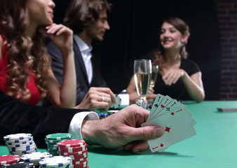 Closeup of poker hand of aces in pastel colors