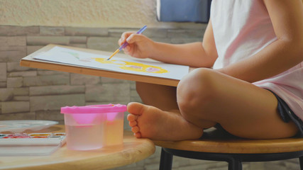 Child girl drawing by watercolor at home.