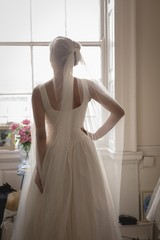 Bride in wedding dress looking through window at boutique