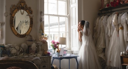 Bride in wedding dress looking through window