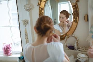 Young bride in wedding dress wearing earrings