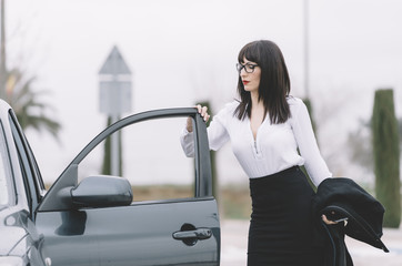 Executive brunette woman with short skirt and glasses poses next to the car.