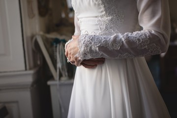 Bride in wedding dress touching her stomach in boutique