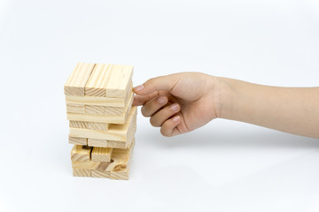 Hand of kid playing a blocks wood tower game of architectural project