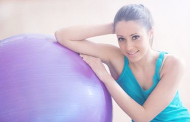 Young woman exercising with physioball at gym