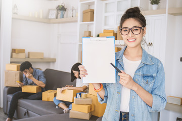 Startup small business entrepreneur SME, asian woman writing clipboard. Portrait of young Asian girl at home office, online marketing packing delivery team, SME teamwork e-commerce concept