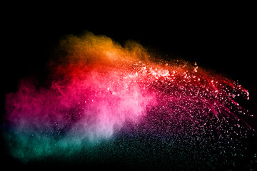 Freeze motion of color particles on white background. Multicolored granule of powder explosion. Abstract color dust overlay texture.