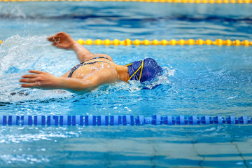 female athlete swimmer swimming butterfly stroke in pool competition