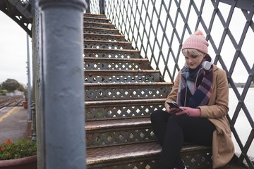 Woman sitting on stairs and using mobile phone