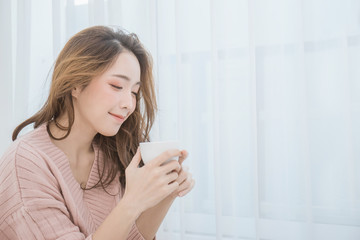 Young beautiful asian woman her hands holding a cup of coffee morning winter time in her white bedroom. Happy cheerful relaxing in cold winter concept.