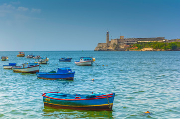 Local fishing boats in Havana, Cuba with El Morro castle in the background