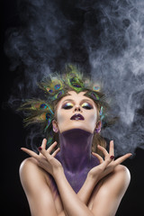 Beautiful big breast girl wearing peacock feathers in her hair and artistic violet shiny body art on her neck, vanguard makeup artistically crossed her hands in theatrical smoke