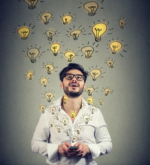 Young man in eyeglasses holding smarpthone and producing plenty of successful ideas.
