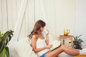 Cheerful woman reading book and drinking tea