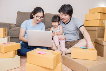 Asian family typing computer with boxes. Start up small business entrepreneur SME freelance asian woman  working box, online marketing packaging box and delivery, SME e-commerce concept