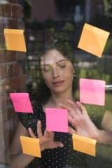 Female executive looking sticky notes