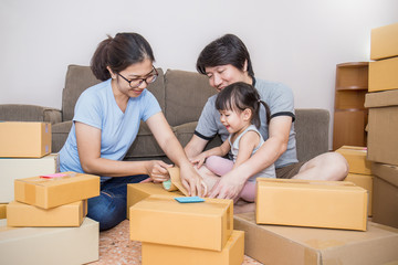 Young happy asian family man woman and girl packing cardboard box in the office SME business, family relocation moving house and small business, SME concept .