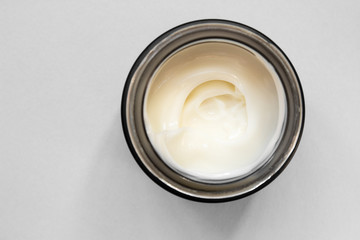 Smear cream with snail mucin in black container. Lotion for face or body. Skin care. Close up