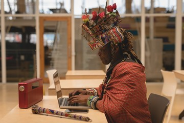 Maasai man in traditional clothing using laptop