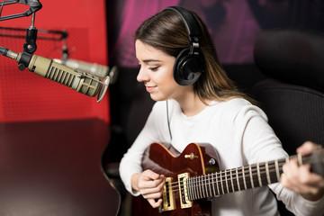 Beautiful singer playing guitar in radio station