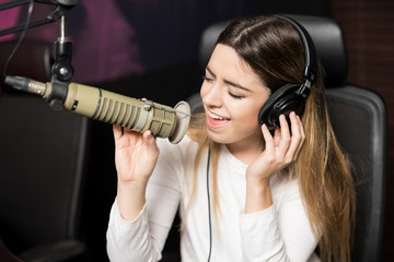 Female singer performing live song at radio station