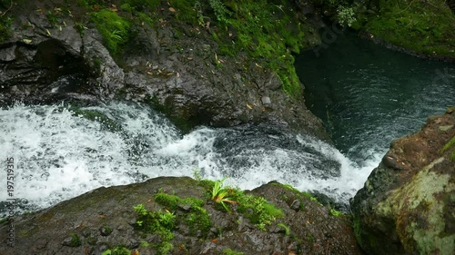 New Zealand: Karamatura Falls. View from above a crystal clear waterfall cascading over mossy rocks into a small pool below. Beautiful nature scene. Waitakere Ranges Regional Park, West Auckland.