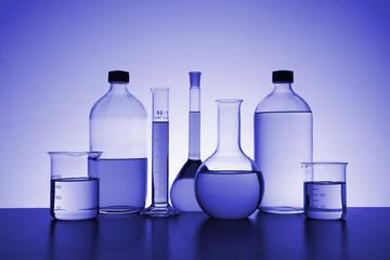 blue monochrome photo of chemical bottles