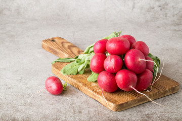 A bunch of young juicy radish with leaves on a wooden cutting board on a gray background.