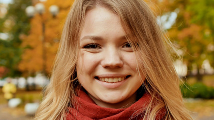 Face of young attractive girl close-up. Smiling girl posing on camera among colorful autumn park trees.
