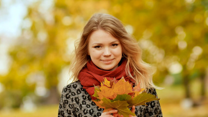 A young girl joyfully posing on the camera with a bouquet of colorful leaves. Walk in the city park in the autumn.