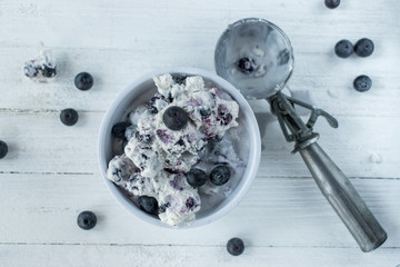 handmade blueberry ice cream in white bowl with scoop on white table top view