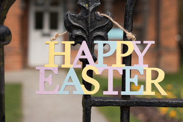 """Sign of """"HAPPY EASTER"""" hangs on slightly opened gate in the background of door of house and garden. Meet the spring holiday of the Great Easter! Welcome to us!"""