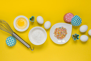 concept of the Easter bakery, various products for home baking, sugar, eggs and flour, coconut munt, top view, empty space for text on a yellow background in the style of pop art mocap layout