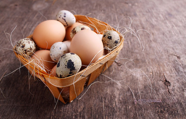 Fresh farmer eggs of chicken and quail in a basket on rustic background