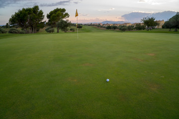 Golf ball on green fairway blue cloudy summer sky in the background