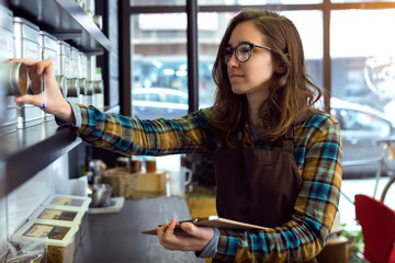 Beautiful young saleswoman doing inventory in a retail store selling coffee.