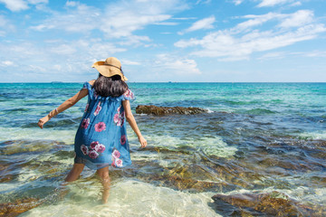 Girl standing in the sea wearing blue dress.
