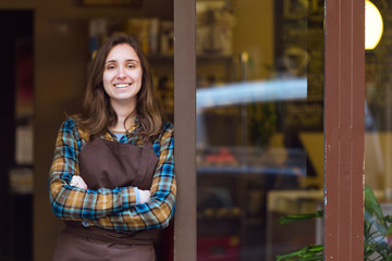 Beautiful young saleswoman looking at camera and leaning against the door frame of an organic store.