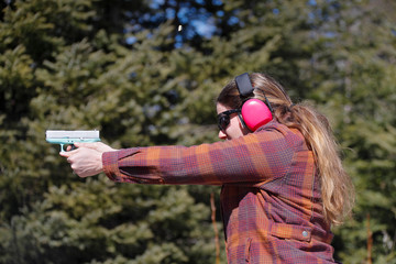 Woman shooting a handgun; ejected cartridge case in the air.