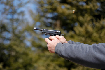 Close-up of a handgun being fired; ejected shell in the air.