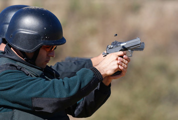 A police officer of the local prison shoots at target during a practice session at a shooting military range in Valparaiso