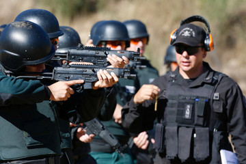 Police officers of the local prison, point at target during a practice session at a shooting military range in Valparaiso