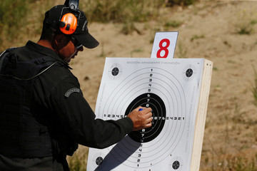 A shooting instructor check a target during a practice session of the Police Officers of the local prison at a shooting military range in Valparaiso