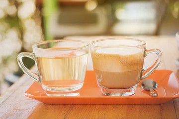 cup of coffee and tea on the orange tray,  when you serve a coffee  you will get tea also