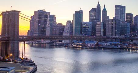 Lights of New York City and Brooklyn Bridge at Sunset