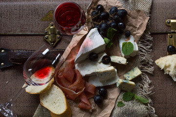 talian antipasta setting. Old cheese, red wine, grape, sundried tomatos in an antique setting
