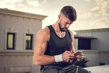 Handsome man using smartphone after sports training outdoors
